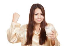 Healthy Asian woman in pajamas fist up with glass of milk Royalty Free Stock Photography