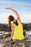Healthy Asian woman practicing yoga at beach wearing yellow top Royalty Free Stock Images
