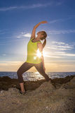 Healthy Asian woman practicing yoga at beach wearing yellow top Stock Photo