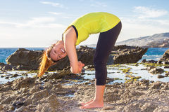 Healthy Asian woman practicing yoga at beach wearing yellow top Royalty Free Stock Photography