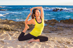 Healthy Asian woman practicing yoga at beach wearing yellow top Royalty Free Stock Photo
