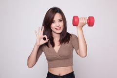 Healthy Asian woman show OK with dumbbells. Royalty Free Stock Images