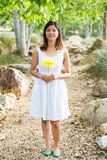 Healthy Asian woman in white dress holding flowers and fruits at green park Royalty Free Stock Photos