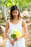 Healthy Asian woman in white dress holding flowers and fruits at green park Stock Images