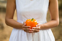 Healthy Asian woman in white dress holding flowers and fruits at green park Stock Image