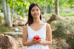 Healthy Asian woman in white dress holding flowers and fruits at green park Stock Photo
