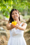 Healthy Asian woman in white dress holding flowers and fruits at green park Royalty Free Stock Image
