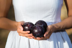 Healthy Asian woman in white dress holding plums at green park Royalty Free Stock Photo