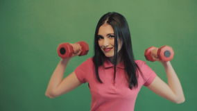 Healthy Asian woman workout in the studio with two dumbbells in front of green background. Shot over green screen.  stock footage