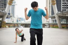 Running competition in the city. Healthy Asian young men winner raise his hands to celebrate running victory while female loser runner fall on floor or footpath Royalty Free Stock Photo