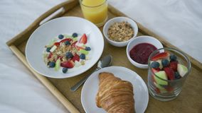 Healthy assorted breakfast served on tray. From above view oh delicious fruit mix served with juice and croissant on wooden tray above white blanket of bed stock footage