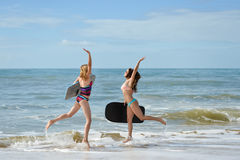 Healthy athletic surfer girl friends with fit bodies holding boards Royalty Free Stock Photography