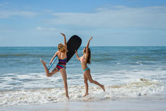 Healthy athletic surfer girl friends with fit bodies holding bodyboards Stock Image