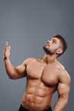 Healthy athletic young man with muscle pointing up stock image