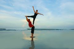 Healthy and attractive fit couple of acrobats  doing acroyoga balance and meditation exercise on beautiful desert beach practicing stock image