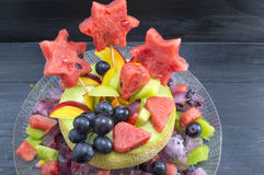 Healthy attractive fruit salad served in a fresh melon against b Stock Photos