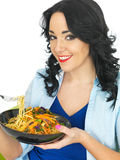 Healthy Attractive Young Woman Eating a Bowl of Fresh Noodles with Stir Fried Vegetables Stock Photo