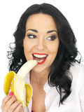 Healthy Attractive Young Woman Eating a Ripe Banana Stock Images
