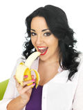 Healthy Attractive Young Woman Eating a Ripe Banana Stock Photo