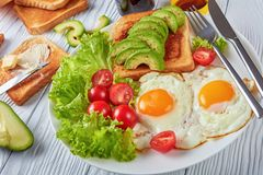 Healthy aussie breakfast on a plate. Healthy aussie breakfast - fried eggs, fresh salad, toasts with yeast spread and sliced avocado served on a white plate on a Stock Photo
