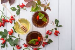 Healthy autumn drink with hip roses ,branch with berries on white  background. Royalty Free Stock Photography