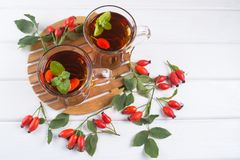 Healthy autumn drink with hip roses ,branch with berries on white  background. Royalty Free Stock Photo