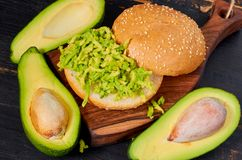 Healthy avocado burger on the wooden board - traditional Mexican dish. Vegetarian avocado sandwich on the black kitchen background royalty free stock photography