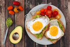 Healthy avocado, egg toasts with tomatoes on rustic wood background Stock Photography