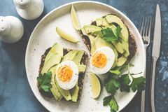 Healthy avocado toasts with boiled egg on a plate stock photos