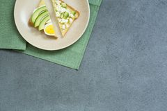 Healthy avocado toasts for breakfast or lunch with bread, sliced avocado and egg. Vegetarian sandwiches, copy space stock images