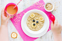 Healthy baby breakfast - oatmeal porridge with fruit. Morning di. Et concept for children. Fun food idea for kids Stock Photos