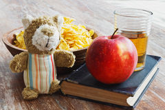 Healthy baby food. Book, apple, glass of juice and a children's toy on a wooden background.  education and nutrition of the child  concept Stock Images