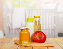 Healthy baby food: milk, juice, puree, apple on  background kitchen. Royalty Free Stock Photos
