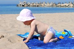 Healthy baby girl playing on the beach Royalty Free Stock Images