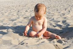 Healthy baby girl playing with sand on the beach Stock Image
