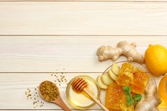 Healthy background. honey, honeycomb, lemon, ginger on white wooden table. Top view with copy space stock image