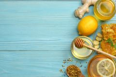 Healthy background. honey, honeycomb, lemon, tea, ginger on blue wooden table. Top view with copy space Royalty Free Stock Photos