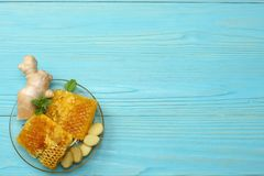 Healthy background. honey, honeycomb, lemon, tea, ginger on blue wooden table. Top view with copy space Stock Image
