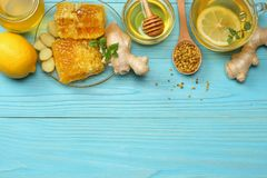 Healthy background. honey, honeycomb, lemon, tea, ginger on blue wooden table. Top view with copy space Stock Photo