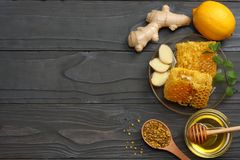 Healthy background. honey, honeycomb, lemon, tea, ginger on dark wooden table. Top view with copy space Stock Photography