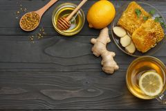 Healthy background. honey, honeycomb, lemon, tea, ginger on dark wooden table. Top view with copy space Stock Photos