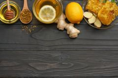 Healthy background. honey, honeycomb, lemon, tea, ginger on dark wooden table. Top view with copy space stock images