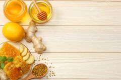 Healthy background. honey, honeycomb, lemon, tea, ginger on white wooden table. Top view with copy space Royalty Free Stock Images