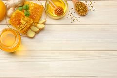 Healthy background. honey, honeycomb, lemon, tea, ginger on white wooden table. Top view with copy space Royalty Free Stock Photo