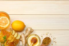 Healthy background. honey, honeycomb, lemon, tea, ginger on white wooden table. Top view with copy space Stock Photos