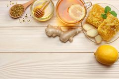 Healthy background. honey, honeycomb, lemon, tea, ginger on white wooden table. Top view with copy space royalty free stock photos