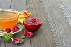 Healthy background. raspberry with raspberry jam, honey and tea on dark wooden background Stock Photo