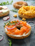 Healthy Bagels breakfast sandwich with salmon, scrambled eggs, vegetables and cream cheese royalty free stock image