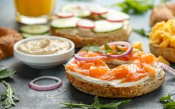 Healthy Bagels breakfast sandwich with salmon, scrambled eggs, vegetables and cream cheese royalty free stock photography