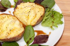 Healthy baked potato with low fat flamed cheese and baby leaf sa. Healthy baked potatoes with low fat flamed cheese and baby leaf salad with balsamic dressing Royalty Free Stock Photo